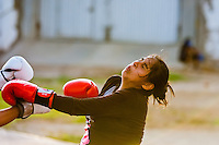 A Peruvian girl is seen being hit while training in the outdoor boxing school at the Telmo Carbajo stadium in Callao, Peru, 4 April 2013.