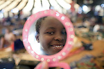 LUDZIDZINI, SWAZILAND - AUGUST 29: An unidentified girl checks herself in a mirror before a traditional Reed dance ceremony at the Royal Palace on August 29, 2009, in Ludzidzini, Swaziland. About 80.000 virgins from all over the country attended this yearly event, which goes on for a week and which is the biggest in Swazi culture. Many of the girls stayed in tents and slept on the ground. It was founded to celebrate the beauty of Swazi women and girls. King Mswati III, and absolute monarch, was born in 1968 and he has 14 wives and many children. The king danced with his men in front of the 80.000 girls. Many of the girls hope to get noticed by the king and to be chosen as a future wife, a ticket from poverty and into a life of privilege and luxury. The country is one of the poorest in the world and it is struggling with a high prevalence of HIV-Aids and severe poverty. (Photo by: Per-Anders Pettersson)...