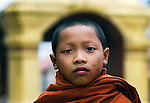 A young Buddhist novice returning to his temple after early morning collection of alms in Luang Prabang, Laos.