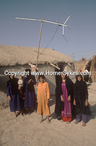 Marsh Arabs. Southern Iraq. Circa 1985. Marsh Arab women and children outside their adobe home with TV aerial banks of River Tigris... Haur al Mamar or Haur al-Hamar marsh collectively known now as Hammar marshes Irag 1984
