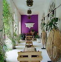A covered terrace with arches opening onto a courtyard swimming pool is filled with an eclectic mix of furniture and objects and punctuated by a bright purple wall