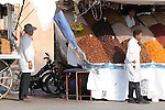Men selling dates and other dried fruits watch the activities on the streets in Marrakesh, Morocco