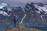 Female hiker takes in mountain view at midnight from Nonstind mountain peak, Vestvågøy, Lofoten Islands, Norway