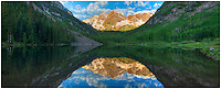This Colorado panorama is a stitch of two images, thus creating an image that attempts to show the width of Maroon Lake in the shadow of the iconic Maroon Bells. The morning was still and the early morning clouds drifted peacefully over the calm, cold waters.