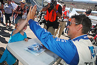 "Scott Pruett ""high fives"" a young fan before the Utah 250 Grand-Am Rolex series race at Miller Morosports Park in Tooele, UT on Saturday, September 19, 2009.  (Photo by Brian Cleary/www.bcpix.com)"