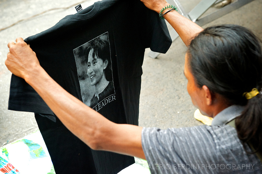 A young supporter of Aung San Suu Kyi checks a T-Shirts on a street market. Something unthinkable just few months before..Mandalay, Myanmar. 2012
