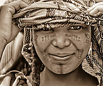 Zalika Amadou, daughter of the former chief of Bele Kwara, Niger no longer lives in the village, but has returned for a visit. Zalika sports the traditional Fulani facial scarring that is considered beautiful. The scarring is done with a razor blade, and charcoal powder mixed with cream is rubbed into the fresh wound to create the darkened effect. Zalika also has had her lower lip and chin died black. This is fdone by piercing the lip with a needle in multiple locations, and then rubbing ground tree seeds into the dried wounds to blacken them.