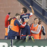 New England Revolution midfielder Diego Fagundez (14) celebrates his goal with teammates.  In a Major League Soccer (MLS) match, the New England Revolution (blue) defeated Columbus Crew (white), 3-2, at Gillette Stadium on October 19, 2013.
