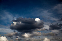 A puff of white cloud peeks from behind a dark gray cloud against a background of blue sky.