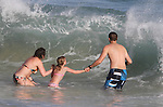 A family reluctantly faces a wave at Sandy's Beach in Honolulu, HI.
