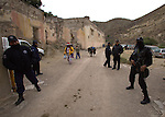 A Native Wixarica walks past between state policemen after his pilgrimage to his sacred place of Cerro Quemado in Wirikuta, February 7, 2012. The scene is at Real de Catorce town in San Luis Potosi state. Photo by Heriberto Rodriguez