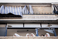 A group of Syrian women watch a demostration from a balcony after the friday prayers in the Bustan Al Qasr district of Aleppo, Syria.