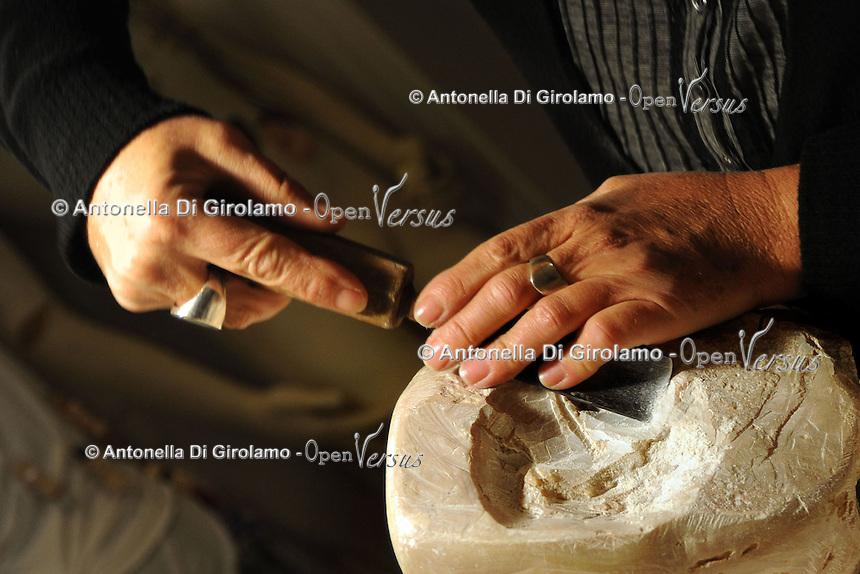 Artisti a San Lorenzo , quartiere storico di Roma. .Jole Falco, scultrice nel suo studio mentre lavora la pietra saponaria..Artists in San Lorenzo, historic district of Rome. .Jole Falco, sculptor in his studio while working saponaria stone........