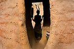 A woman of the Tamberma people is silhouetted in a simple doorway structure in her village in Togo. She is wearing a traditional headdress made of impala horns, giving her silhouette unique form.