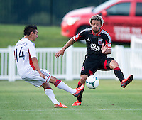 Nick DeLeon (18) of D.C. United tries to block the cross of Diego Fagundez (14) of the New England Revolution during the quarterfinals of the US Open Cup at the Maryland SoccerPlex in Boyds, Md.  D.C. United defeated the New England Revolution, 3-1.