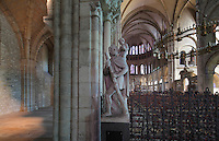 North side aisle (left) and the nave and choir (right), with a statue of St Christopher in the foreground, in the Basilique Saint Remi or Abbey of St Remi, Reims, France. The 11th century, mainly Romanesque, church, contains the relics of St Remi, the Bishop of Reims, who converted Clovis, the King of the Franks, to Christianity in 496 AD. The abbey is a UNESCO World Heritage Site. Picture by Manuel Cohen