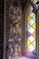 A detail of one of the shell-encrusted window surrounds with sunlight puring through the stained glass window