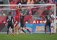 Toronto, Ontario - May 3, 2014: New England Revolution goalkeeper Bobby Shuttleworth #22 jumps for a ball as Toronto FC defender Steven Caldwell #13 tries to make contact during a game between the New England Revolution and Toronto FC at BMO Field.<br /> The New England Revolution won 2-1.