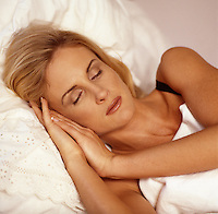 Stock Photo of a Blonde Woman with her head on a pillow lying asleep in her bed