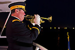 Freeport, New York, USA. 10th Sept. 2014. A bugler plays taps at night on board the boat Miss Freeport V, which sailed from the Woodcleft Canal of the Freeport Nautical Mile after a dockside remembrance ceremony in honor of victims of the terrorist attacks of September 11 2001. American Legion, Patriot Guard Riders, and Captain Frank Rizzo hosted the ceremonies on the eve of the 13th anniversary of the 9/11 attacks.