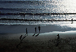 Silhouetted activities and shadows on the beach. El Medano,Tenerife, Canary Islands.