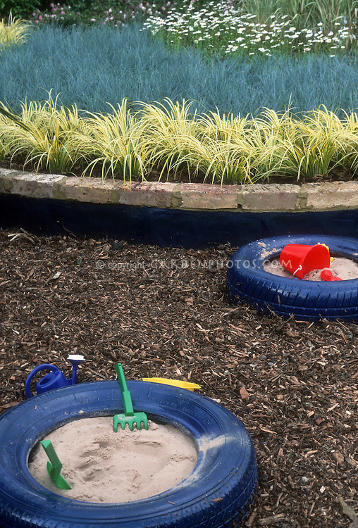Uses for recycled tires tyres for child's sand box play with toys shovels and watering cans next to ornamental grasses in the garden