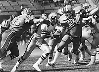 Los Angeles Express quarterback Tom Ramsey is sacked by Oakland Invader Cedrick Hardman and #91.<br />(1983 photo/Ron Riesterer)