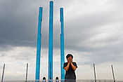 Japanese artist, Hitori Nakayama poses for a portrait in front of his sculpture, Celebration of Our Blue Sky, a set of four 25-meter tall pillars soaring vertically into the sky in the UNESCO heritage city of Georgetown in Penang, Malaysia. Photo: Sanjit Das/Panos