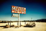 Abandoned desert motel sign on highway under a blue sky