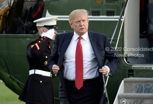 United States President Donald Trump walks on the South Lawn of the White House after disembarking from Marine One in Washington, DC, April 9, 2017.<br /> Credit: Olivier Douliery / Pool via CNP