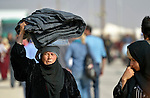 A woman carries blankets on her head as she walks in the Zaatari Refugee Camp, located near Mafraq, Jordan. Opened in July, 2012, the camp holds upwards of 20,000 refugees from the civil war inside Syria. International Orthodox Christian Charities and other members of the ACT Alliance are active in the camp providing essential items and services.