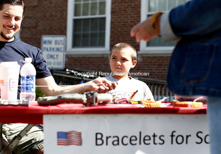 Middlebury, CT- 15 September 2013-091513CM02-  Andrew Widlar, 10, of Middlebury and his father Mike Widlar make survival bracelets out of paracord during St. John of the Cross' 19th annual Apple Harvest Festival in Middlebury Sunday morning.  Proceeds from the bracelets will go towards wounded American soldiers. The annual event featured games, crafts, food, and a tag sale. Proceeds from the fair will go towards parish.      Christopher Massa Republican-American