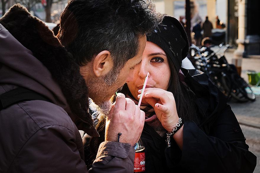 Nederland, Amsterdam, 19 maart 2015<br /> Toeristen drinken samen een flesje cola.<br /> Foto: Michiel Wijnbergh