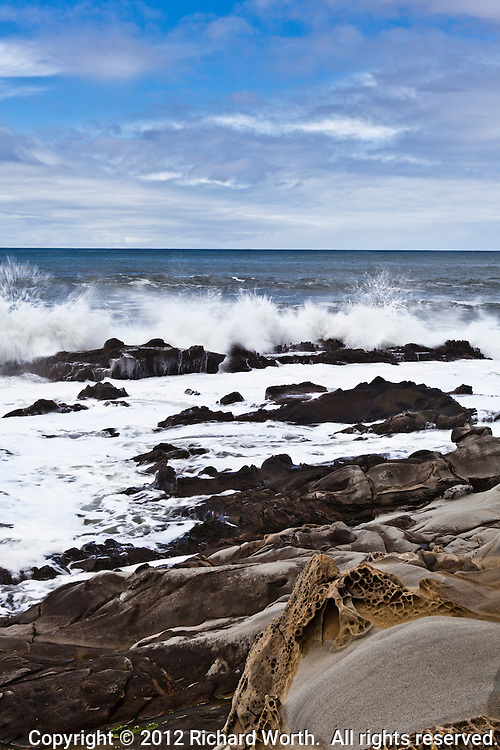 A wave slams into rocks at California's Bean Hollow State Beach sending spray skyward with the craggy and tafoni sculpted beach in the foreground and the ocean for background and a clouded sky overseeing it all.