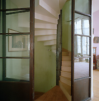 Glass doors lead off the wooden staircase into the living room