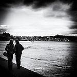 Couple walk arm in arm along the old Scarborough sea front, castle visable in the background with dark skies and choppy waters.