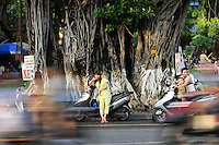 A woman leans against a scooter as traffic passes by on a street in Hanoi, Vietnam, Tuesday, September 5, 2006. Photo by Servais Mont/Pictobank