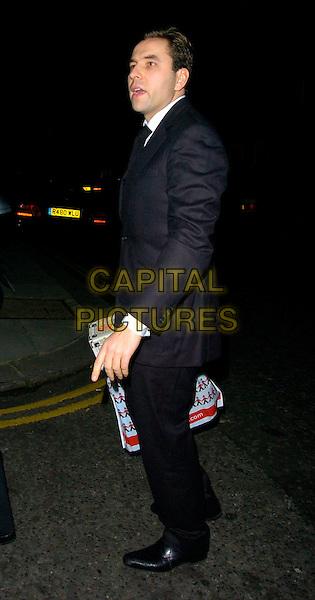 DAVID WALLIAMS.Sharon Osbourne's Christmas Party, 30 Pavillion Road, London, UK..December 19th, 2006.full length black coat suit Hamley's bag.CAP/CAN.©Can Nguyen/Capital Pictures