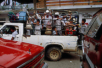 Farm families crowd in a truck on the way home from an Indian market. Streets are clogged on Sunday in this small mountain town. Chaos dominates a normally quiet Huastec village when the narrow streets fill with people buying and selling locally grown coffee and sugarcane, copal incense and huge corn tamales.<br /> <br /> South of Ciudad Valles the Pan American Highway passes through Huasteca Indian country in Mexico. Huastec population was once estimated to be one million, but today they number about 150,000.