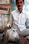 A man sits with a severed goat's head at a butcher store in Kolkata, India