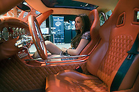 Moscow, Russia, 24/10/2009..A model in a sports car at the Millionaire Fair in Moscow. The event has become an annual fixture, attracting thousands of would-be and existing Russian millionaires to view and purchase a wide range of luxury goods. This year however the fair was much smaller, an indication of how the formerly booming Russian economy has been hit by the world financial crisis.