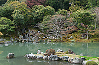 A stone jetty juts out into the ornamental lake in the Zen gardens at Tenryu-ji Temple, Kyoto