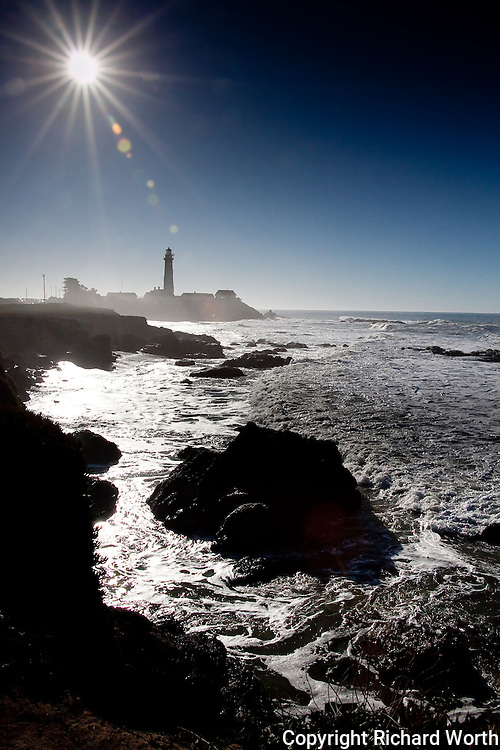 Under clear blue skies and a bright blazing sun the Pigeon Point Lighthouse stands tall on the California coast.