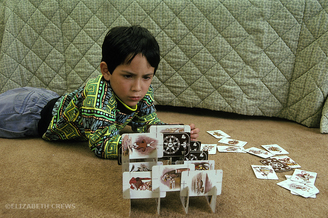 """San Diego CA Latino boy, 6, concentrating on building with """"house of cards"""""""