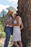 sexy cowboy and girl about to kiss while standing under a tree in New Mexico