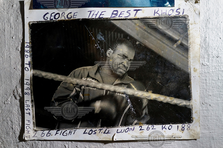 An old photograph of George Khosi, founder of the Hillbrow Boxing Club, annotated with his boxing record.  Hillbrow, in downtown Johannesburg, is the city's most notorious neighbourhood. It is overcrowded, ridden with illegal squats and suffers from high levels of crime much of which is related the thriving illicit drug trade. Against this backdrop, George Khosi's story is not atypical. A childhood spent on the streets, where he survived by committing petty crime and hustling, led to imprisonment at the age of 16. Because he was big and looked older than his age this incarceration was in an adult institution. Here he began to fight since, as he says 'they wanted to make me a woman and I didn't want to be a woman.' When he got out, he took up boxing in earnest. His prospects as a professional boxer looked bright until he was shot and left for dead during a burglary. He lost his right eye and now walks with a limp. His boxing career seemed over but George picked up his gloves again, this time to teach Hillbrow's youngsters. His gym became a place of hope and discipline for local youth, keeping them of the streets and even producing some national champions.