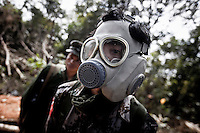 A KIA soldier uses a gas mask to protect himself as he fears for the chemical bombs shelling by Burmese army during months of fighting in Maiya Jang front line, the second largest city under control of the Kachin Independence Army. The KIA positions around the city have been attacked by shelling and heavy artillery during months. Fierce clashes have taken place since the ceasefire was broken out by the Burmese army last June 2011. During months the fighting were spread out along the Kachin State leaving more than 40,000 displaced persons and refugees (a conservative estimating) in accord with the humanitarian aid groups.