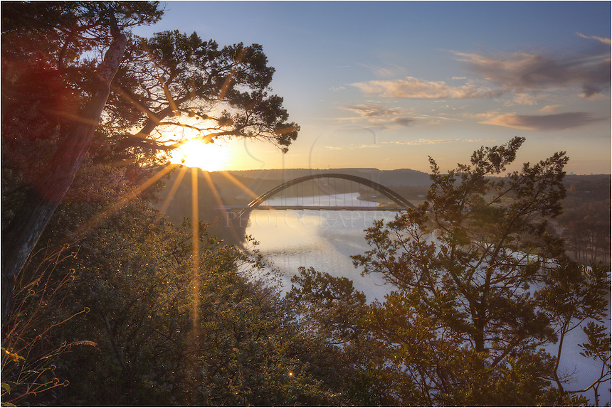 Through the trees, the sun peeks through on a cold December morning. This Pennybacker Bridge image shows the 360 Bridge with the Colorado River flowing underneath. It was cold this morning, but the sunrise was beautiful over Austin, Texas.