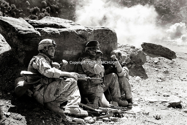 US Embedded Tactical Trainer (ETT) SGT Clark (R), who has just been shot in the left arm and had another round stopped by his chest plate, has his wound bandaged by Staff Sergeant Anderson (C) from White Platoon, Able Company, 3/71 Cav, 10th Mountain Division, while Staff Sergeant Sears,also from White Platoon, shouts to other soldiers nearby, all while under fire during an ambush near Kamu outpost in Nuristan Privince, north-east Afghanistan, 14 May 2007. Elements of White Platoon were called upon, along with US Embedded Tactical Trainers (ETTs) and ANA from 1st Company, 2nd Kandak, 201st Corps, Afghan National Army, to act as a Quick Reaction Force to a nearby earlier ambush, but minutes after coming accross the first of the dead and wounded they were engaged by insurgents heavily dug into the mountainsides and got caught up in a major firefight. By the end of the day there were 15 ANA dead, 4 wounded, and one believed captured by insurgents. 6 US personnel and 1 Irish photographer were also wounded during the fight. (John D McHugh)