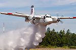 A Calfire Grumman S2-T Turbo Tracker based in Grass Valley, California, drops a load of water the length of the runway during a demonstration at the Nevada County Airport. The Turbo Tracker is a civilian conversion of the Navy's S-2 Tracker. The Calfire fleet, formerly California Department of Forestry, includes 23 of the Turbo Trackers located throughout the state. Each aircraft is capable of carrying 1200 gallons of water or retardant and able to reach a fire within 20 minutes.
